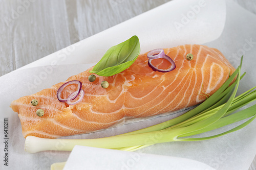 Ready to bake raw salmon steak and leek on white baking paper