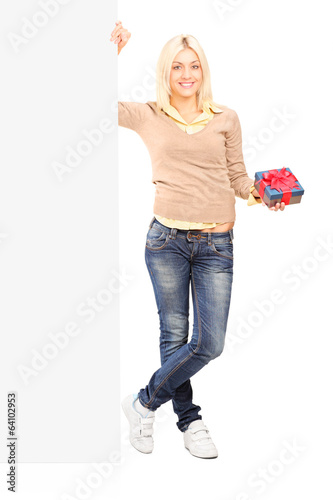 Girl holding a present next to a blank panel