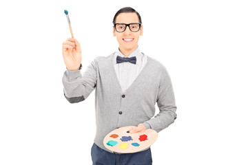 Male artist holding paintbrush and a color pallet