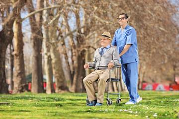 Male nurse pushing a senior in wheelchair outside