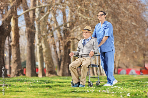 Male nurse pushing a senior in wheelchair outside