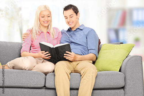 Man and woman reading a book seated on sofa