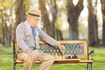 Senior adult playing chess outdoors