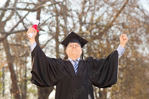 Mature graduate gesturing happiness outdoors