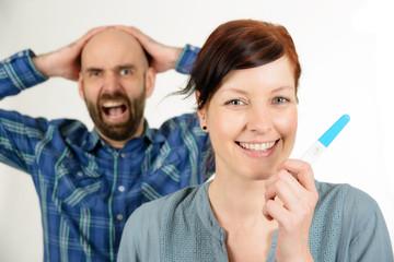 Lachende Frau und verzweifelter Mann mit Schwangerschaftstest