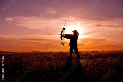 Woman Bowhunter in Sunset - 64106362