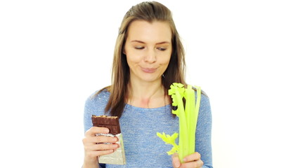 Woman choosing healthy vegetable over chocolate, isolated