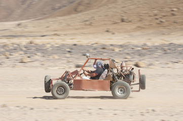 Desert buggy racing across ground