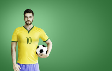 Brazilian player holds a soccer ball on green background