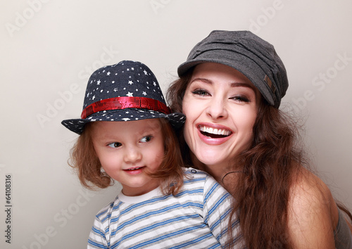 Happy trendy family in caps. Laughing mother and fun kid girl