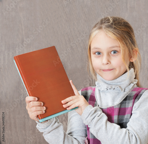 girl holding books on a wooden background