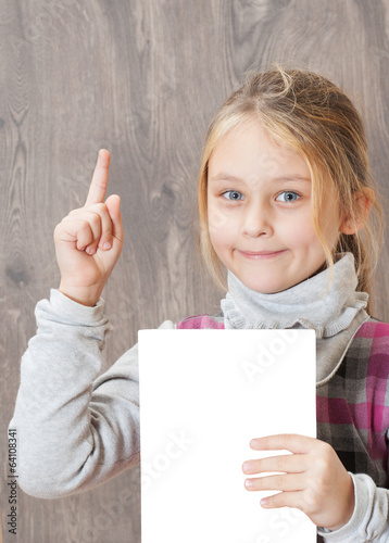 little girl holding a sheet of white paper and points finger up
