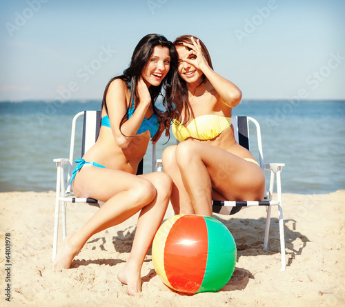 girls sunbathing on the beach chairs