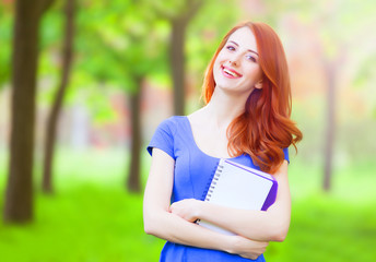 Portrait of young redhead smiling woman with notebook in the cit