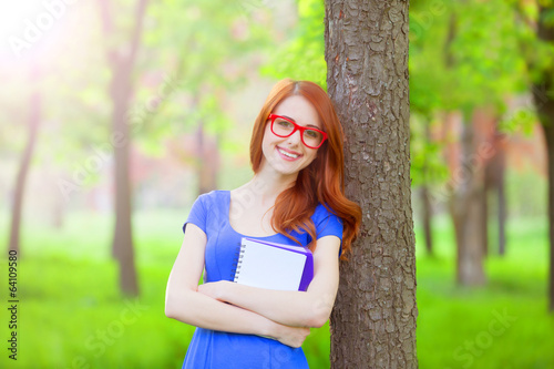 Portrait of young redhead smiling woman in glasses and with note