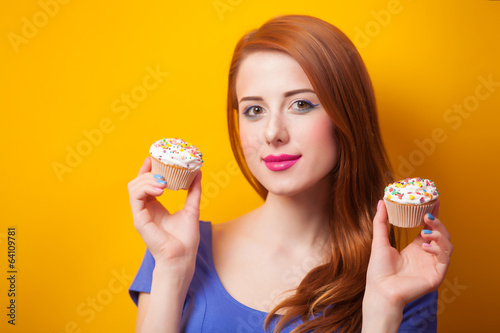 Redhead women with muffin on yellow background.