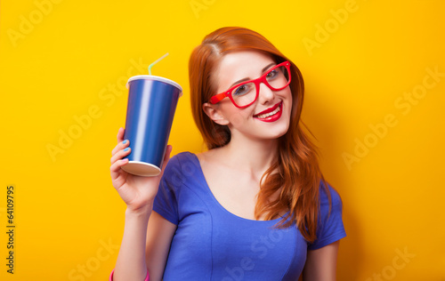 Redhead girl with drink and glasses on yellow background.