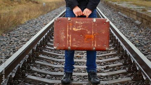 Boy holding a suitcase on railway