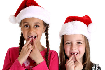 girls wearing santa hats missing their two front teeth
