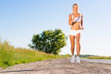 jeune femme athlétique courir sur la route