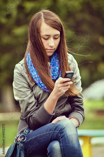Young woman reading an sms on her mobile