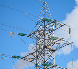 High voltage power lines and large pylon above blue sky