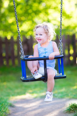 Funny toddler girl in playground at swing on sunny day