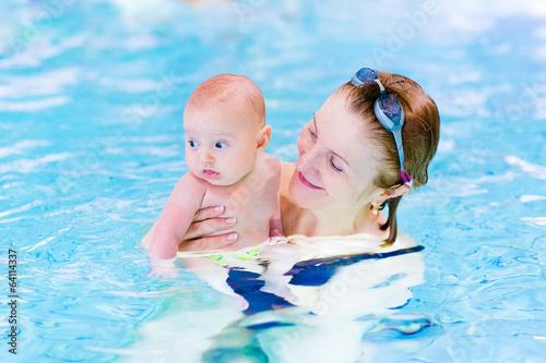 Young active woman enjoying swimming pool with baby boy