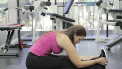 Young woman with sports body stretching and relaxing at the gym