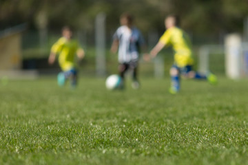 Three kids playing soccer