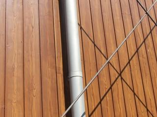 Regenrohr und Verstrebungen aus Metall an einem Neubau