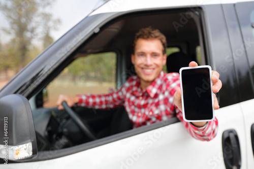 Smart phone man in car driving showing smartphone