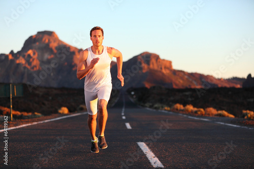 Athlete running sprinting at sunset on road