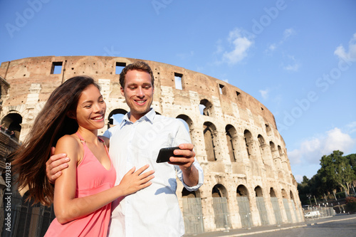 Couple in Rome by Colosseum using smart phone