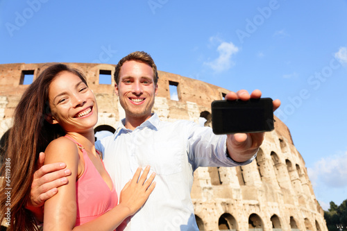 Couple showing smartphone in Rome by Colosseum