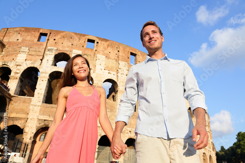 Couple in Rome by Colosseum walking holding hands