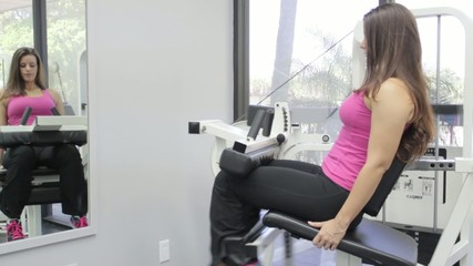 Woman at the gym exercising her legs on a machine