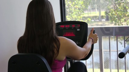 Woman exercising on a stationary bike in a gym