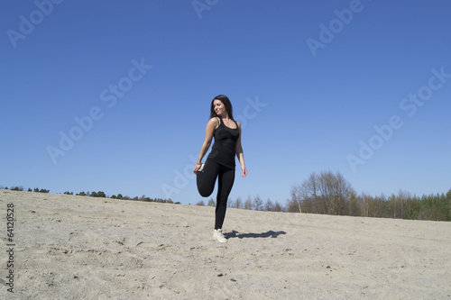 Woman stretching / working out at the beach (sunny day)