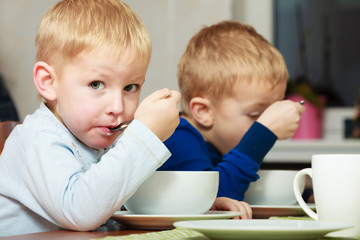 Boys kids children eating corn flakes breakfast at the table