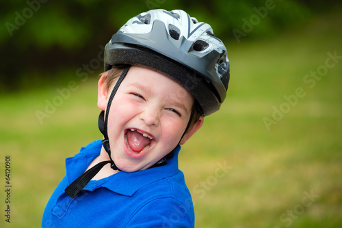 Happy child wearing a bike helmet outdoors