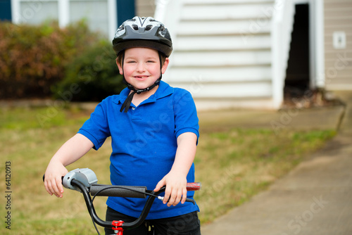 Happy child riding his bike outside his home
