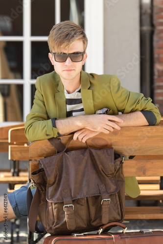 Young handsome man with bag waits on bench