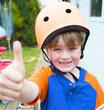 little boy wearing a cycling helmet giving thumbs up