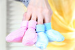 Hands with crocheted booties for baby, on light background
