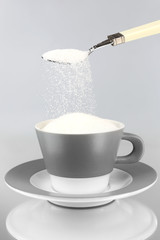 Sugar in cup on grey background