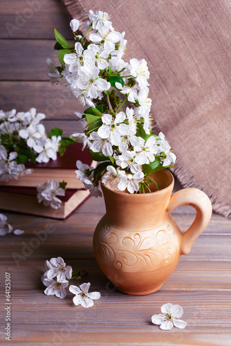 Beautiful fruit blossom in pitcher on table on grey background