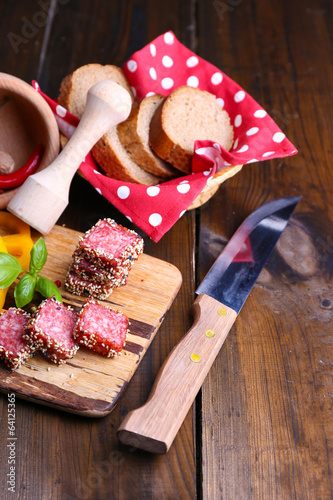 Composition of knife,    sliced salami sausage with sesame,