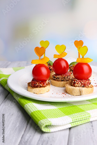Tasty canapes with salami,tomato, pepper  and basil leaves,