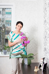 Happy mature woman with Phalaenopsis orchid indoor